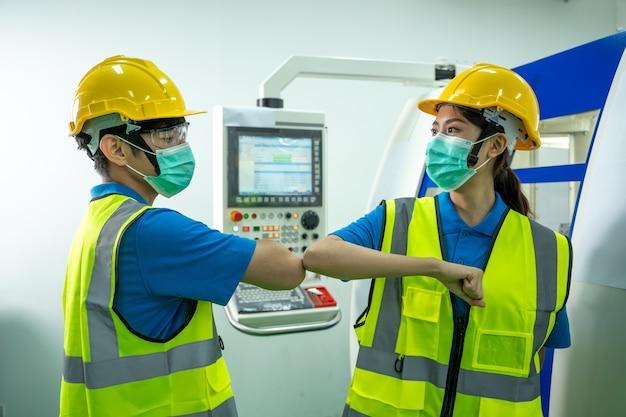 공장에서 팔꿈치를 부딪히는 인사를하는 보호 얼굴 마스크를 착용하는 공장 노동자