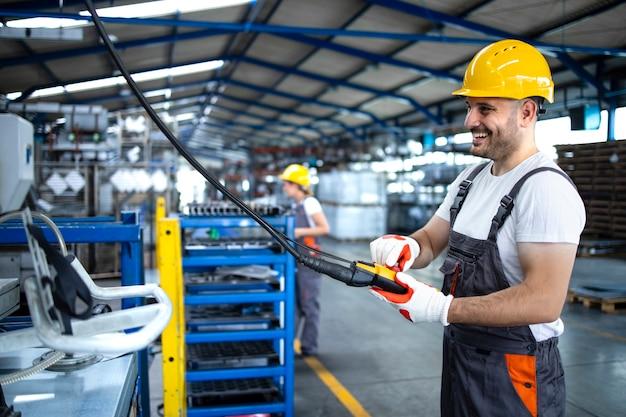 생산 홀에서 푸시 버튼 조이스틱으로 산업 기계를 작동하는 유니폼 및 안전모를 착용하는 공장 노동자