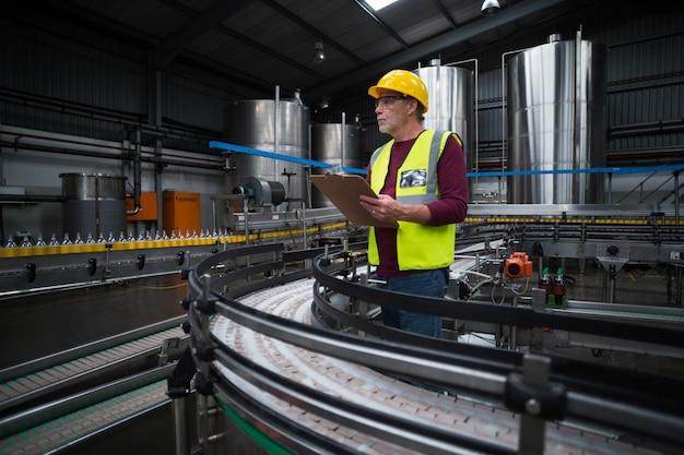 Фабричный рабочий с буфером обмена работает на фабрике