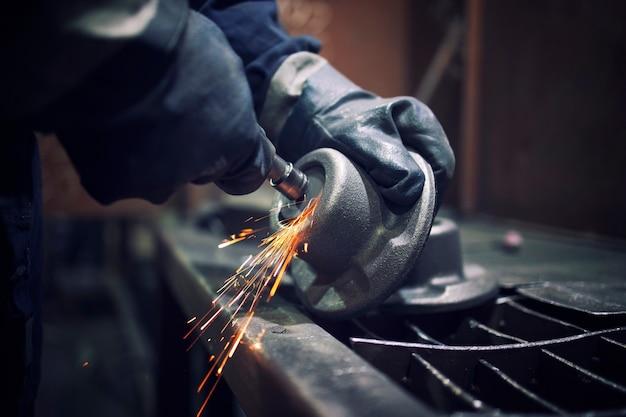 Заводской рабочий с точильщиком формирует металлическую деталь и летят искры.