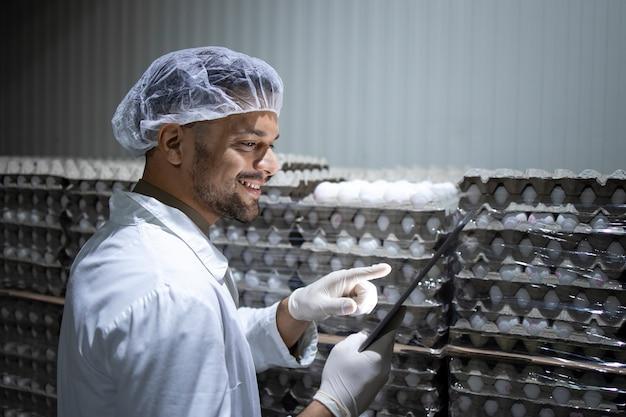 헤어 넷 및 위생 장갑이있는 공장 노동자는 태블릿 컴퓨터를 들고 차가운 식품 보관소의 재고를 확인합니다.