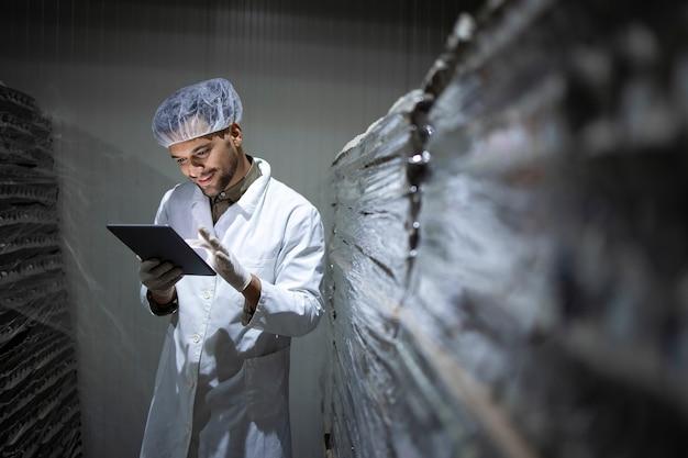 헤어 넷 및 위생 장갑 공장 노동자는 태블릿 컴퓨터를 들고 식품 냉장 보관 재고를 확인합니다.
