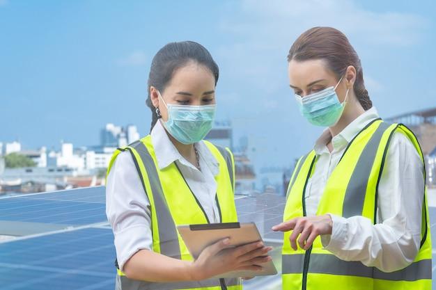 태양 전지 패널 옥상에서 검사하기 위해 마스크 회의를 하는 공장 노동자 여성
