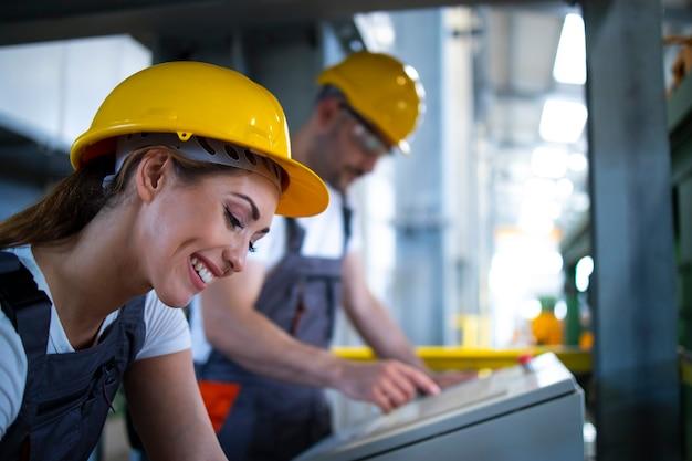 Operai nella sala di controllo che azionano macchine industriali a distanza nella linea di produzione