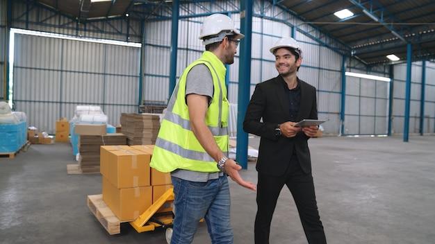 Рабочие фабрики доставляют пакеты коробок на толкающей тележке на склад. концепция управления цепочкой поставок отрасли.