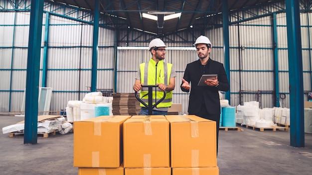工場労働者は、倉庫内のプッシュトロリーで箱のパッケージを配達します。業界のサプライチェーン管理の概念。