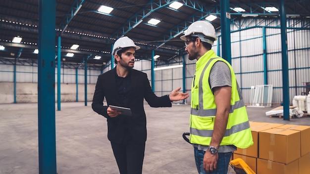 Рабочие завода доставляют коробки с упаковкой на толкающей тележке на склад. концепция управления цепочкой поставок отрасли.