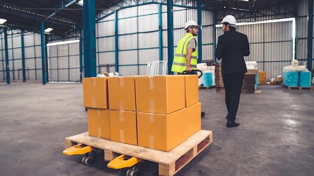 Рабочие фабрики доставляют пакет коробок на толкающей тележке на склад