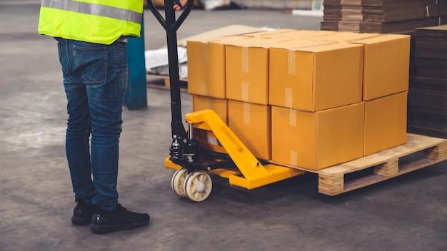 공장 작업자는 창고의 추진 트롤리에 상자 패키지를 배달합니다.