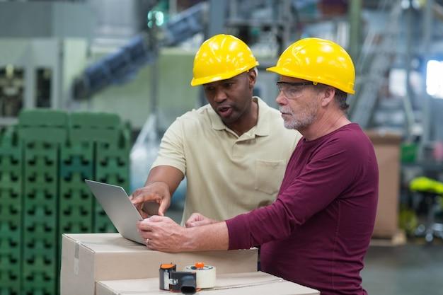 飲料製造工場でラップトップに取り組んでいる間議論する工場労働者