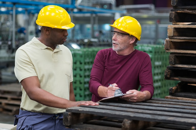 ドリンク製造工場でクリップボードと議論する工場労働者