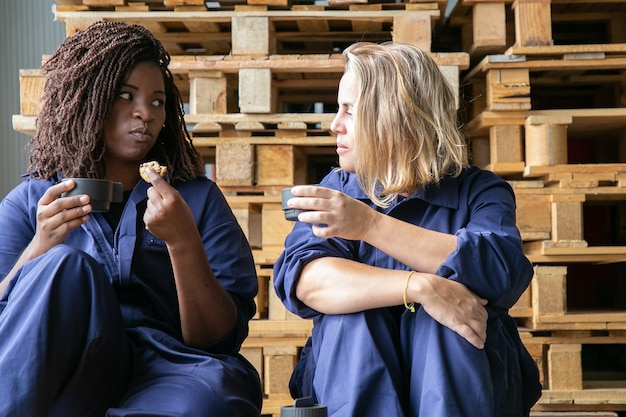 Factory workers drinking coffee, eating cookies, sitting at wooden pallets and chatting