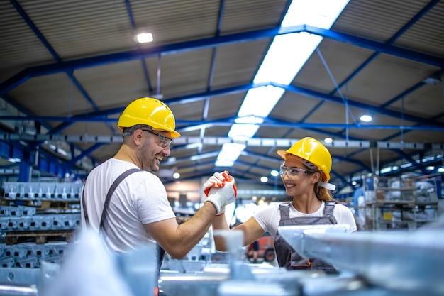 생산 라인에서 서로 인사하는 공장 노동자