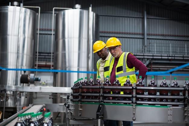 飲料製造工場で冷たい飲み物のボトルを監視する工場労働者
