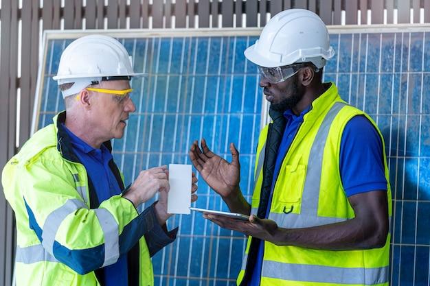 지속 가능한 기술을 위해 태양 전지 패널을 보여주고 확인하는 공장 노동자