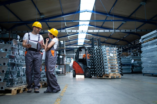 Factory workers standing in industrial warehouse and discussing about production