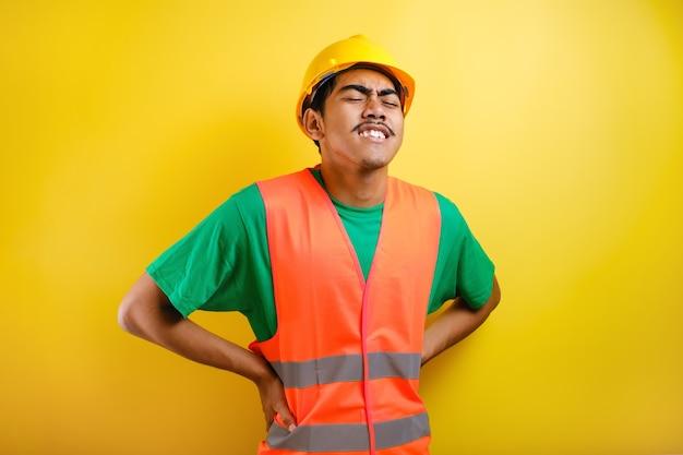 工場労働者は疲れて、ハードワークで背中の筋肉を燃え上がらせます。黄色の背景に対して腰痛の症状を伴う工場労働