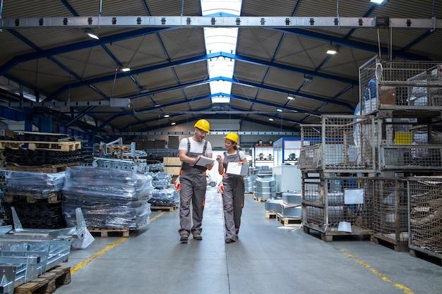 Заводские рабочие проходят через большой производственный цех и разговаривают