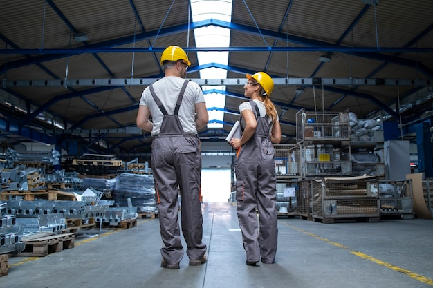 Factory workers walking through large production hall and having conversation