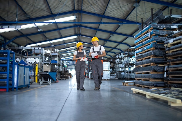 Factory workers in work wear and yellow helmets walking through industrial production hall and discussing about delivery deadline