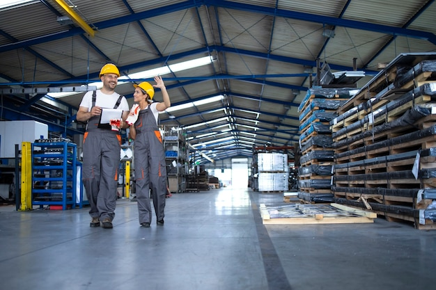 Factory workers in work wear and yellow helmets walking through industrial production hall and discussing about organization