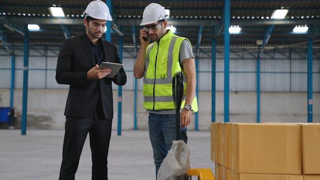Заводские рабочие работают и обсуждают производственный план на заводе