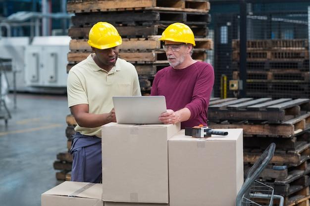 ドリンク製造工場でラップトップに取り組んでいる工場労働者