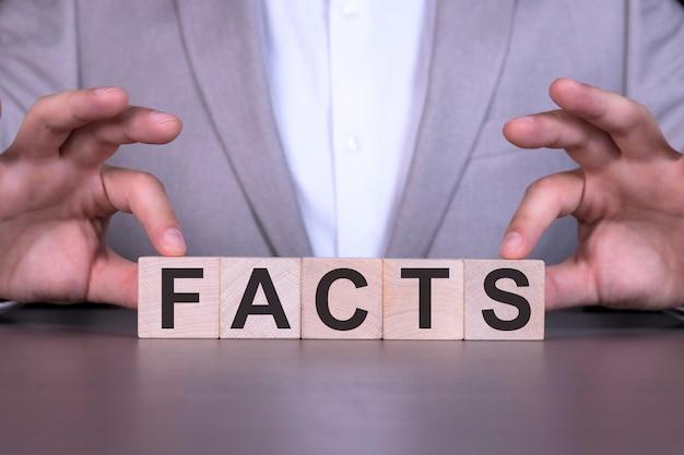 事実、単語は男の背景に、木製の立方体に書かれています