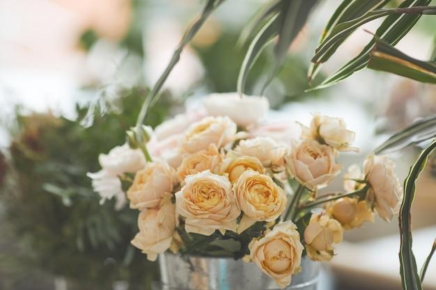 Выцветшее фоновое изображение красивых бледных роз, расположенных в цветочной композиции в мастерской зеленых флористов, копией пространства