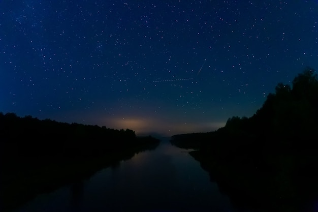 The fading stars in the early morning sky are reflected in a quiet river. the trace of a flying plane intersects with the trace of a falling asteroid in the night sky.