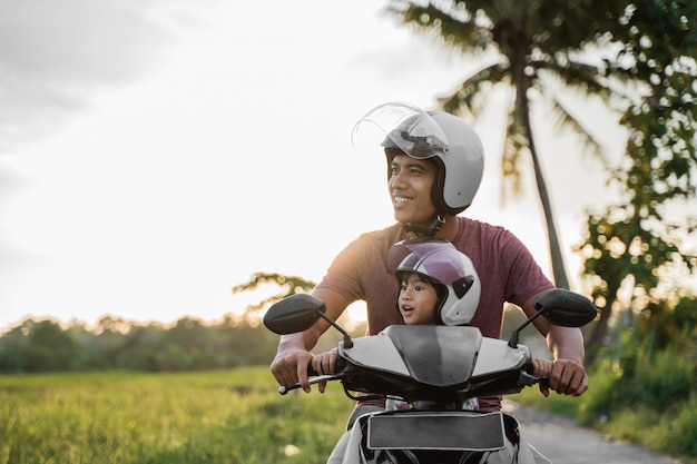 ファーターと彼の子供はバイクのスクーターに乗って楽しむ