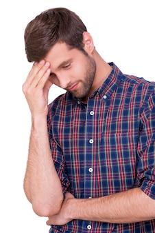 再び失敗しました。カジュアルなシャツを着た欲求不満の若い男が手で額に触れ、白で孤立して立っている間目を閉じたまま