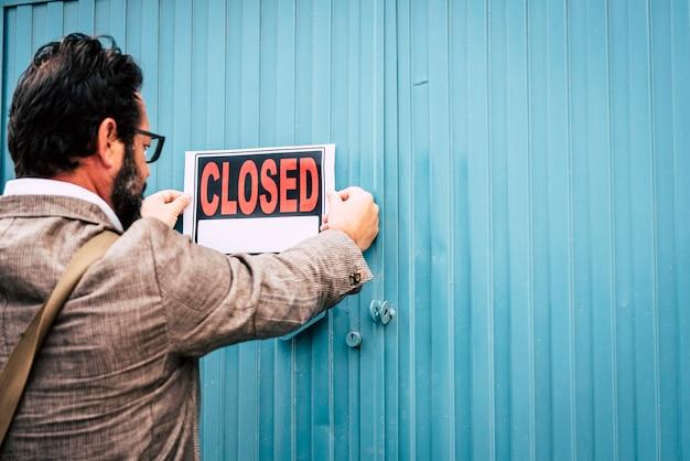 Владелец магазина-неудачник с закрытыми вывесками на двери своего магазина