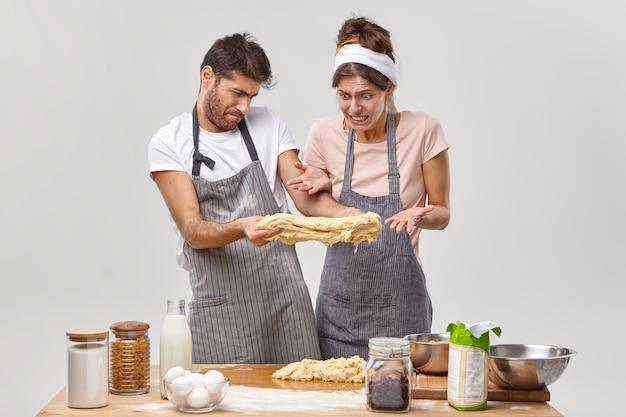 失敗と料理のコンセプト。失望した女性と男性は生の粘着性のある生地を伸ばし、自家製ピザを作るのにいくつかの問題があります、本当の台所の災害、嫌な顔で見る、テーブルの上の台所用品