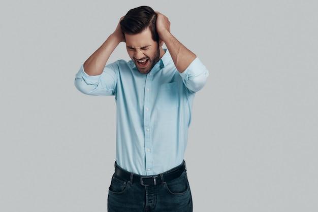 Отказ. разочарованный молодой человек держит голову в руках и гримасничает, стоя на сером фоне