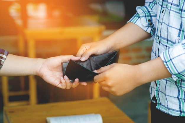 재정의 실패, 돈의 부족, 수입의 부족, 실업, 손과 지갑, 같은 지갑을 들고 있는 두 남자. 소득 부족, 돈 부족, 돈 없는 노동 조건을 보여줍니다.