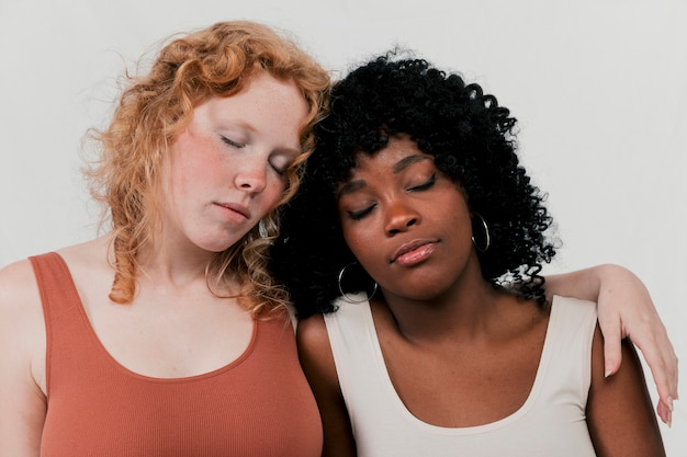 Fair and dark skin women leaning to each other sleeping against grey background