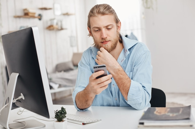 金髪のひげを生やした男性のフリーランサーがスマートフォンに新しいアプリをインストールし、コンピューターにプログラムをダウンロードし、wi-fiを使用し、パートナーからのメッセージを受信します。ビジネス、現代技術、通信