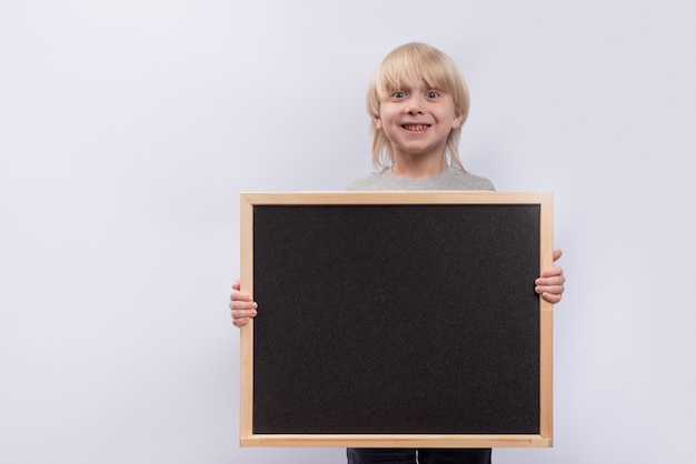 Fair-haired boy holding blackboard and smiling