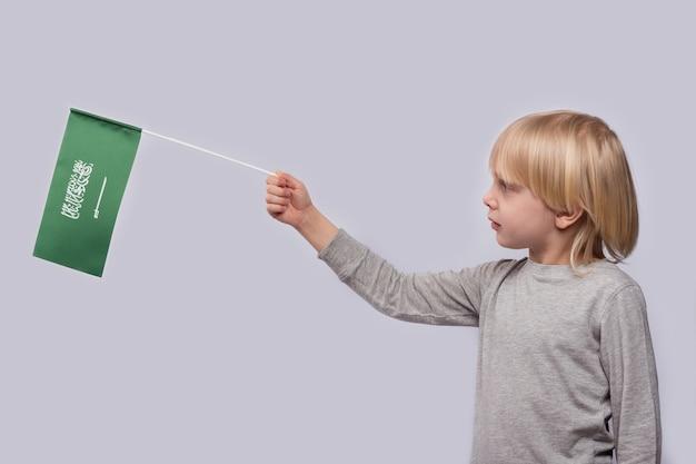 Светловолосый мальчик держит флаг саудовской аравии на белом