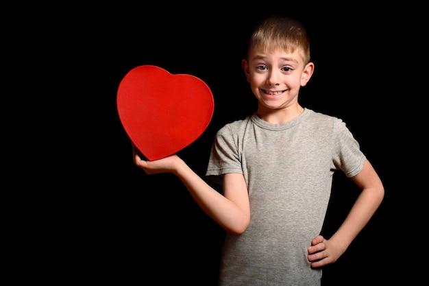 머리 불공평-소년은 검은 배경에 그의 손에 빨간 하트 모양의 상자를 보유하고 있습니다. 사랑과 가족 개념.
