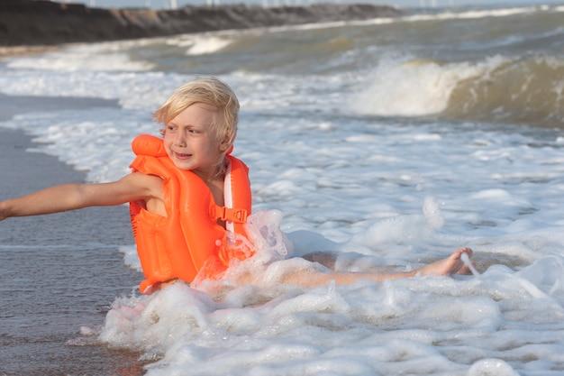 Светловолосый мальчик в надувном плавательном жилете сидит на берегу моря в воде
