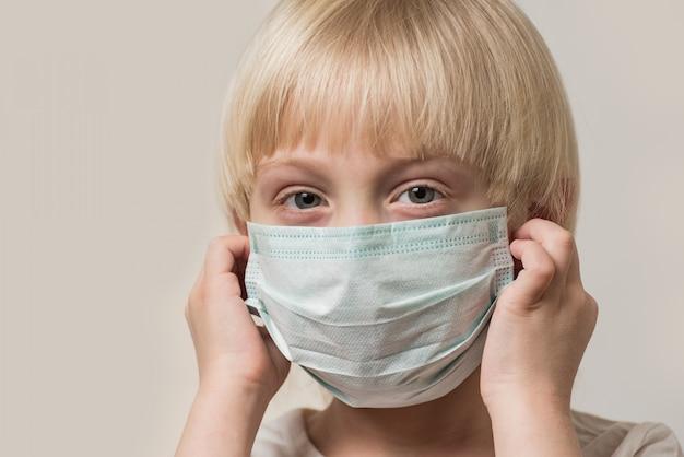公正な髪の少年は無菌の医療用マスクを着ています。インフルエンザに対するマスク保護を身に着けている子供