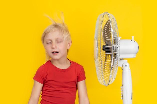 노란색 배경에서 휴식을 취하는 팬이 있는 머리가 좋은 소년. 뜨거운 여름.