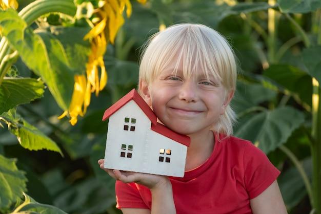 Светловолосый мальчик с домиком окружен полем подсолнухов. экологичный дом. зеленые дома.