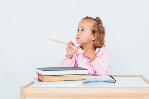 学校の金髪の女の子、テーブルの横にある椅子に座って、鉛筆を持って、考えて笑っている