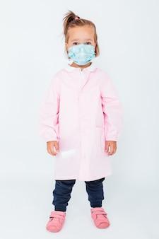 ピンクの子供用エプロンとサージカルマスクを身に着けてcovid-19から身を守る金髪の少女