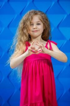 青い背景にピンクのドレスを着て踊ったり笑ったり、明るい子供たちの喜びの感情、幸せな子供時代の金髪の少女