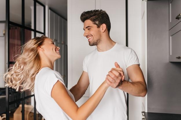 Bella ragazza bionda che balla con l'uomo a casa. ritratto dell'interno di giovane donna che si diverte con il fidanzato.