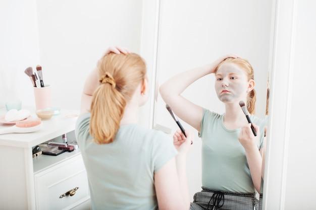 金髪の十代の少女はフェイスマスクを置く